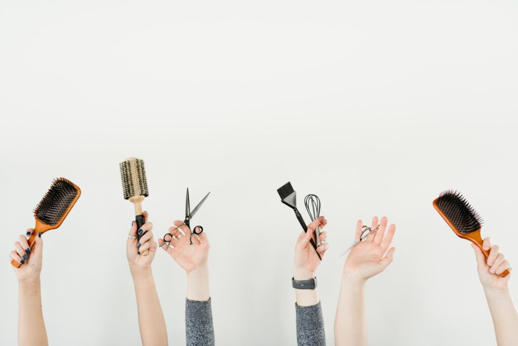 Holding up different brushes and tools.