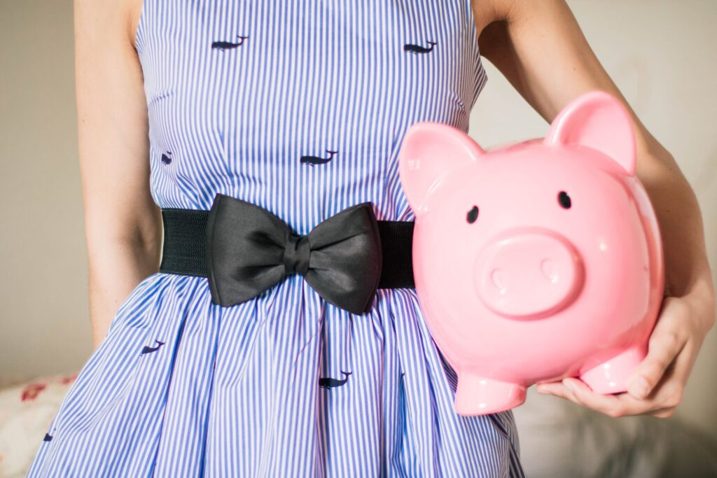 woman in dress holding a piggy bank